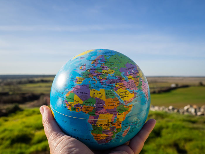 Cropped hand holding globe against blue sky