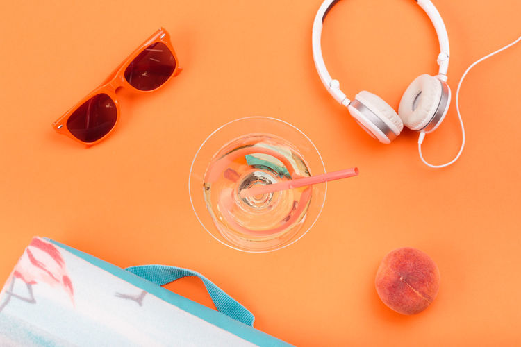 Sunglasses, glass with drink, headphones, peach, blanket on orange background. Minimal summer style Orange Color Blanket Food Drink Fruit Headphones Listening To Music Music Listening Sunglasses Freshness Fresh Lifestyles Minimal Nobody Style Outdooors Peach Bright Summer Summertime Glass Wine Flat Lay