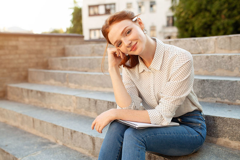 Young beautiful red-haired girl with Semester Student Student Life Students Day Adult Beautiful People Beautiful Woman Casual Clothing Education Emotion Exam Females Front View Hairstyle Lifestyles One Person Outdoors Red Hair Sitting Staircase Steps And Staircases Studying Women Young Adult Young Women