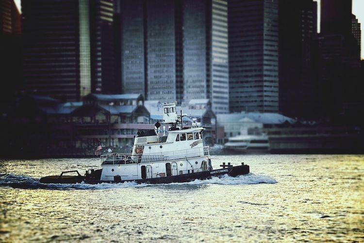 Tugboat In Sea Against Modern Buildings