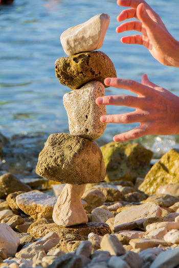 Cropped hand stacking stone on beach against by sea