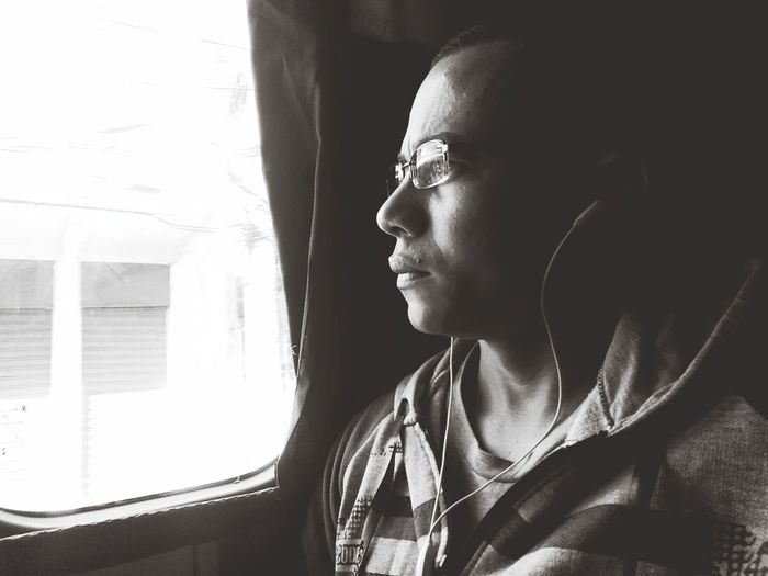 Close-up of man listening music while looking through window