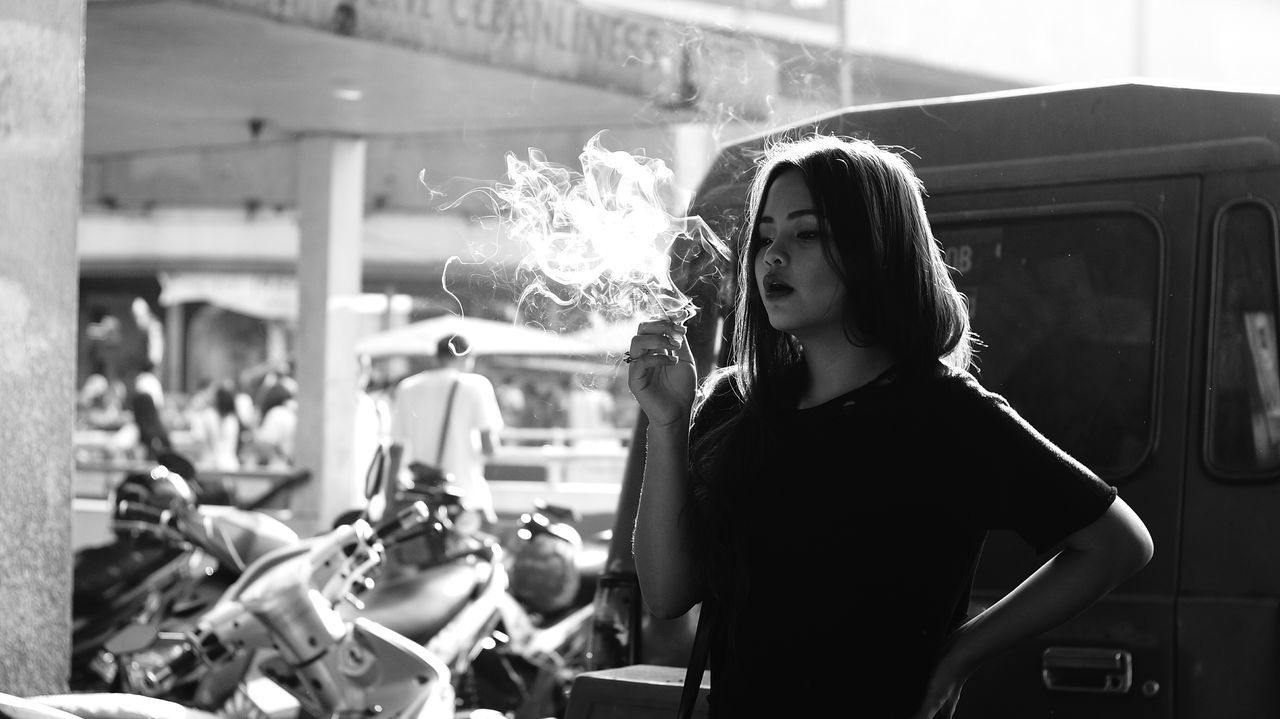 Young woman smoking cigarette on street
