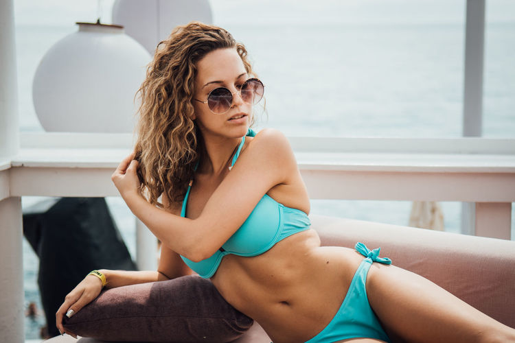 Young Adult One Person Sitting Young Women Clothing Beautiful Woman Hairstyle Lifestyles Real People Beauty Leisure Activity Swimwear Relaxation Bikini Three Quarter Length Hair Fashion Adult Outdoors