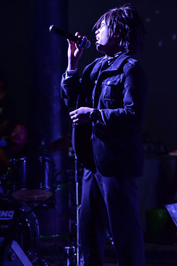 Young singer performing on stage at night
