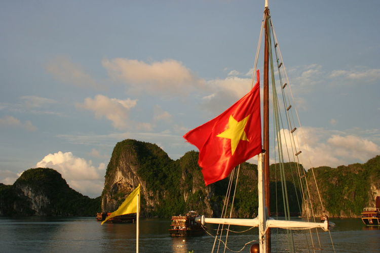 Scenic view of flag by sea against sky