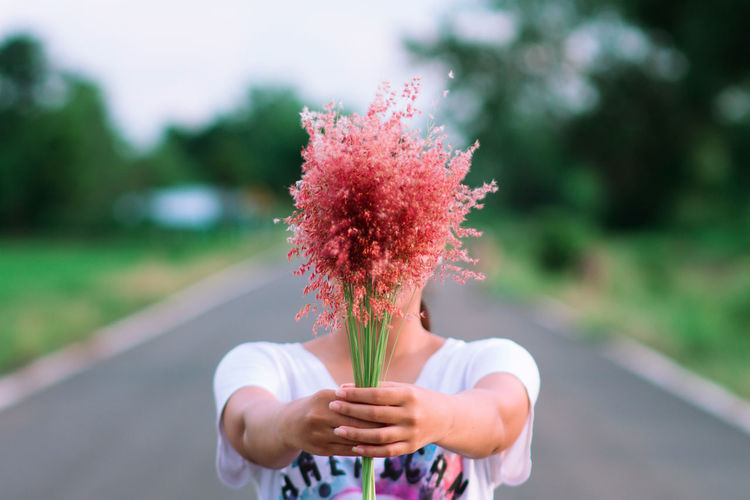Close-Up Of Woman Holding Flowers On Road