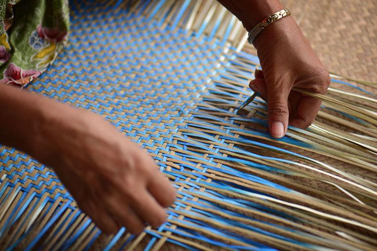 Cropped hands making wicker art