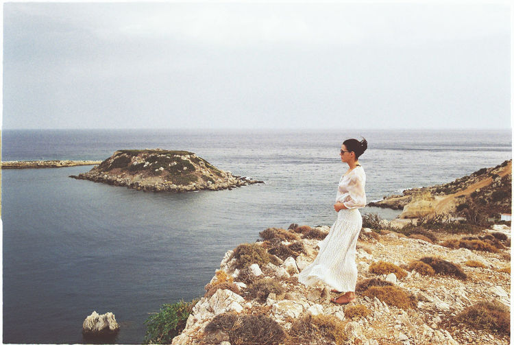 Side view of woman looking at sea while standing on rock against clear sky