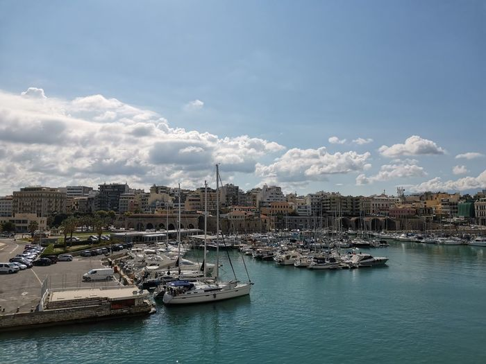 Sailboats moored in harbor by buildings against sky