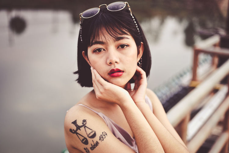 Portrait of beautiful young woman with tattoo on her arm