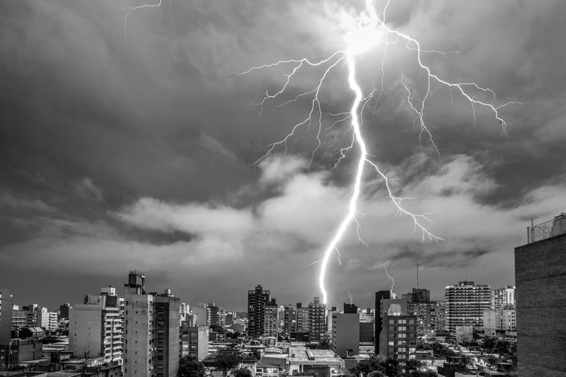 Forked lightning over cityscape against dramatic sky