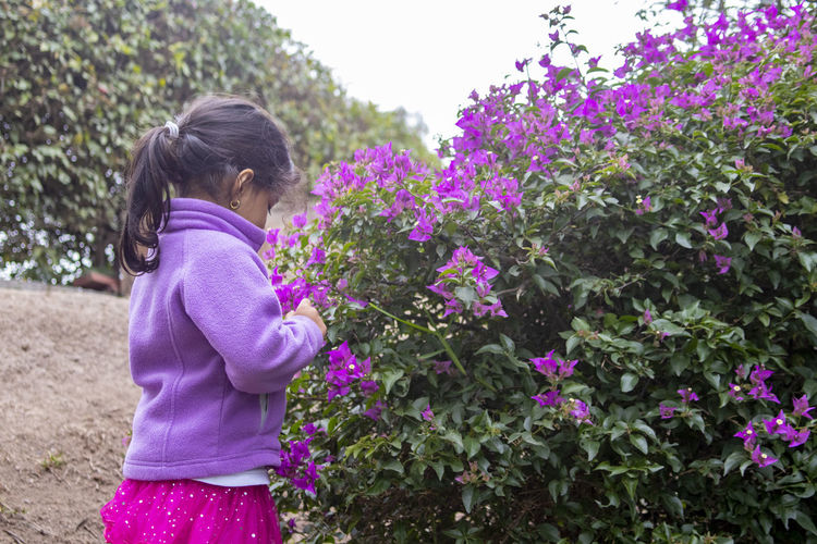 Side View Of Girl Smelling Lilac Flowers At Park