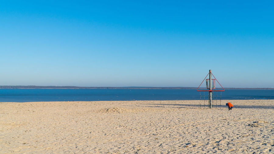 Boy by structure at beach against clear blue sky