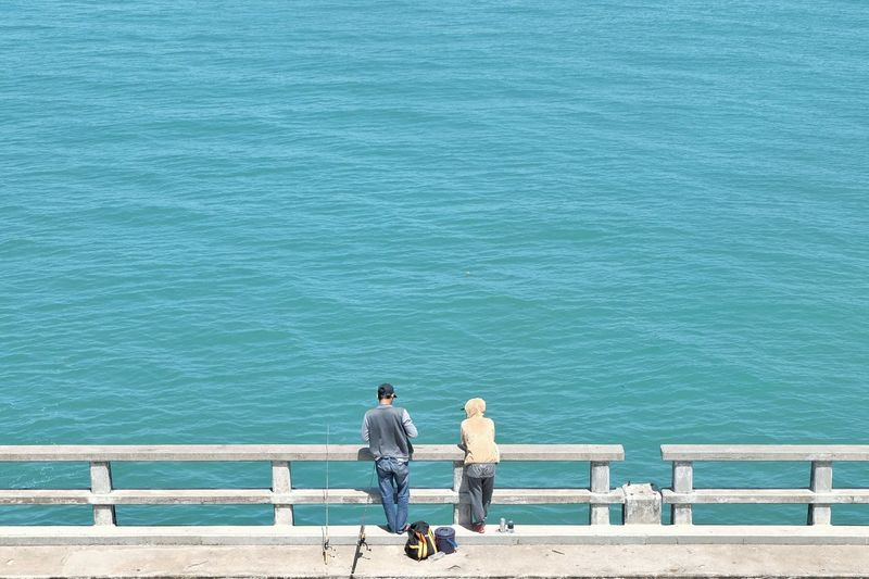 Rear view of people fishing while standing on pier by sea