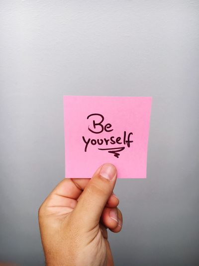 Cropped Hand Of Person Holding Be Yourself Text On Adhesive Note Against Gray Background