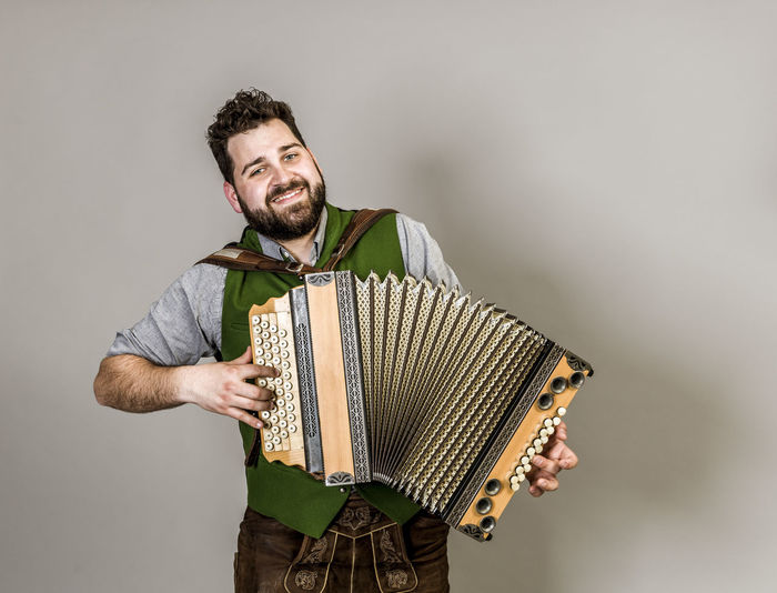 Musician Costume Leather Trousers Tradition Traditional Austria Green Pose Accordion Man Young Shorts Friendly Proud Happy Play Music Fun Joy Single One Background Copy Space Studio Entertainment Mountains Shirt STAND Hobby Leisure Cool One Person Front View Young Adult Indoors  Casual Clothing Standing Smiling Studio Shot Mid Adult Adult Holding Gray Background Waist Up Young Men Three Quarter Length Arts Culture And Entertainment Men