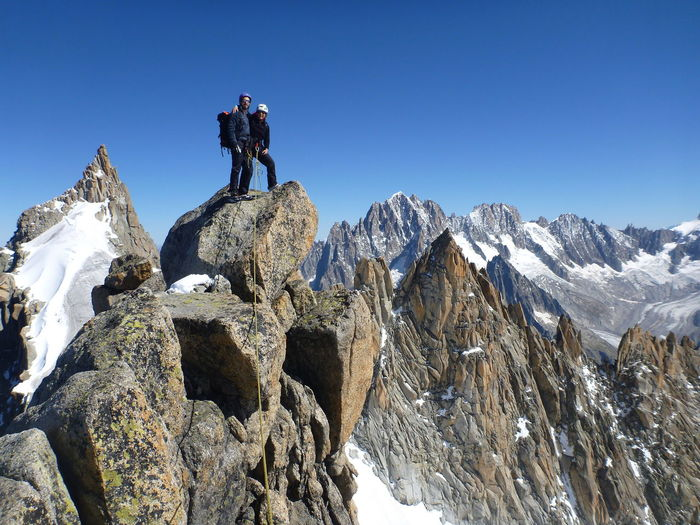 Low angle view of people standing on rock against clear blue sky