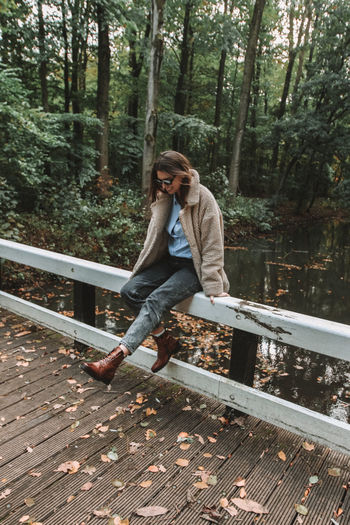 Tree One Person Full Length Plant Young Adult Forest Casual Clothing Day Leisure Activity Front View Real People Lifestyles Nature Clothing Sitting Young Women Adult Outdoors Autumn Autumn colors Girl Woman Bridge Lifestyle