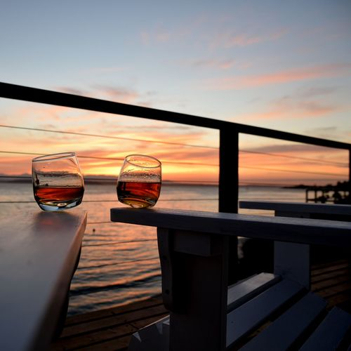 Wineglass On Bench At Boat Deck Against Sky During Sunset