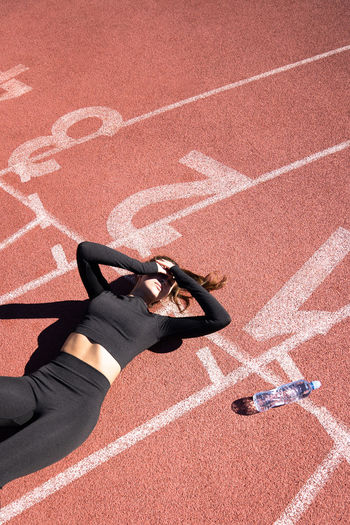 High angle view of tired woman lying with water bottle on running track
