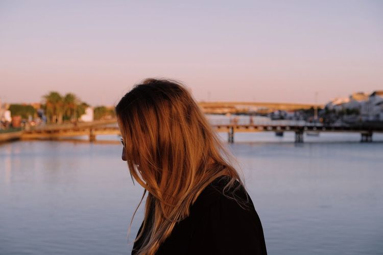 Side view of woman standing against river during sunset
