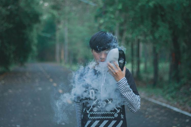Man smoking while holding mask outdoors
