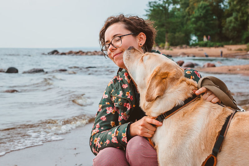 Midsection of woman with dog on beach