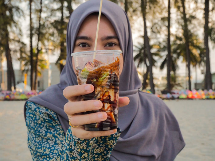 A woman show the Rojak Buah (Fruit Salad in Malay style) for the audience Malay Woman Rojak Buah Plastic Cup Fruit Fruit Rojak Portrait Looking At Camera Front View Close-up Hazel Eyes  Wearing