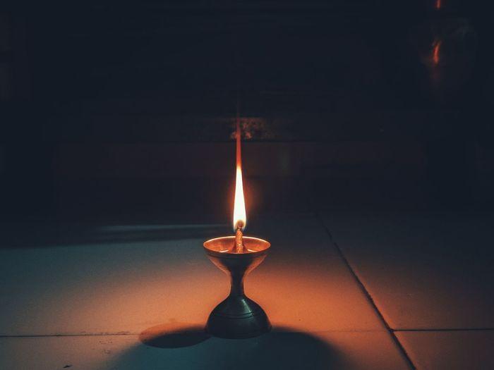 Close-up of illuminated lamp on floor in darkroom