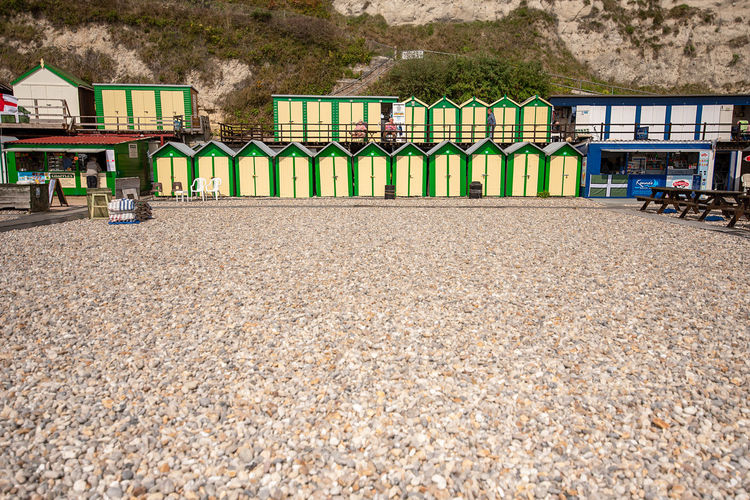 A row of freshly painted traditional wooden beach huts at the bottom of white chalk cliffs in front of the pebble beach of Beer, Devon, UK. Beer Devon Devon Coast South England Beach Huts Beach Sheds Beer Cove Devon Fishing Village For Hire Holiday Huts Jurassic Coast Pebble Beach Rentals Seaside Village Sheds South Coast Tourist Attraction  Traditional Architecture Built Structure Nature Day No People Land Building Exterior Tree Building Multi Colored Outdoors Side By Side Plant Mountain Beach House In A Row City Beach Hut Protection Gravel