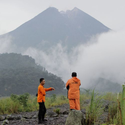Rear view of men standing on mountain road