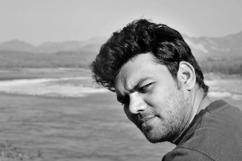Portrait of man at beach against sky