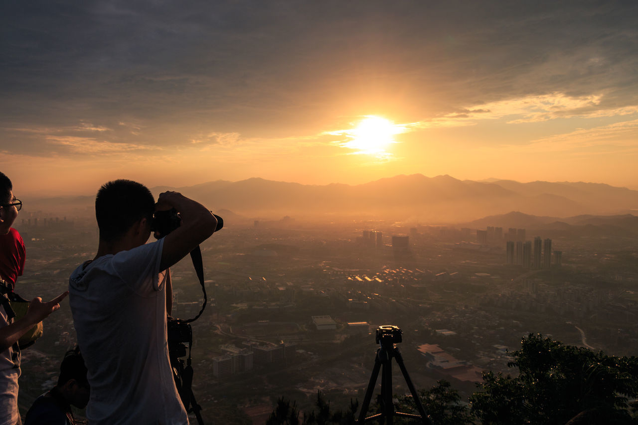 Man photographing sunset over landscape