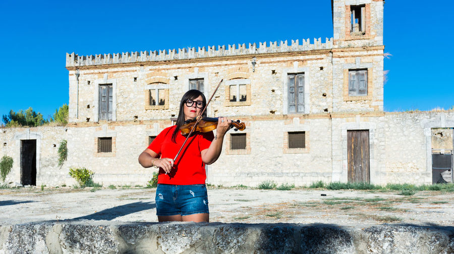 Violin Violinist Woman Woman Portrait Architecture Building Exterior Built Structure One Person History Musical Instrument The Past Sky Music Day Building Clear Sky Musician Arts Culture And Entertainment Sunlight Travel Destinations String Instrument Blue Standing Artist Outdoors