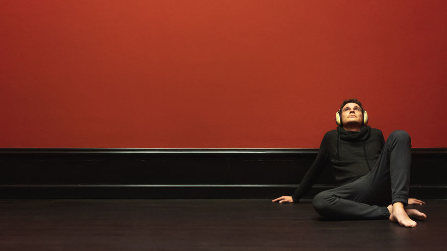 Portrait of young man sitting on red wall