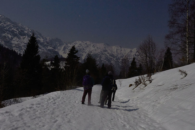 Tourists On Snow Covered Road With Mountains In Background