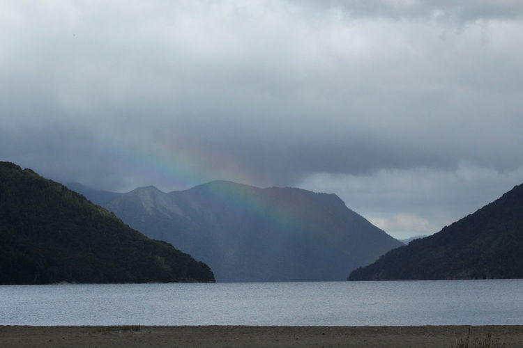 Scenic view of rainbow over sea and mountains against sky
