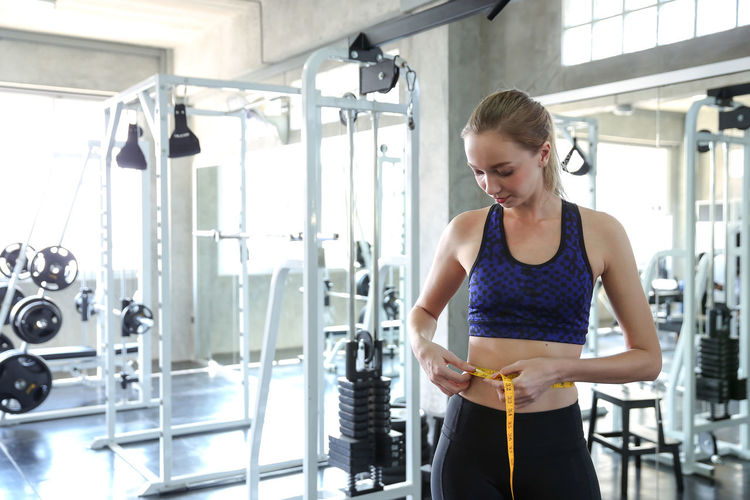 Young woman measuring waist in gym