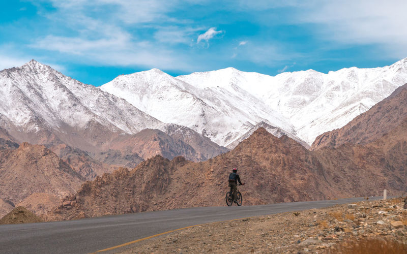 Rear View Of Man Riding Bicycle By Mountains