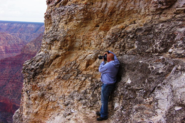 Side View Of Man Photographing Through Camera While Standing On Mountain