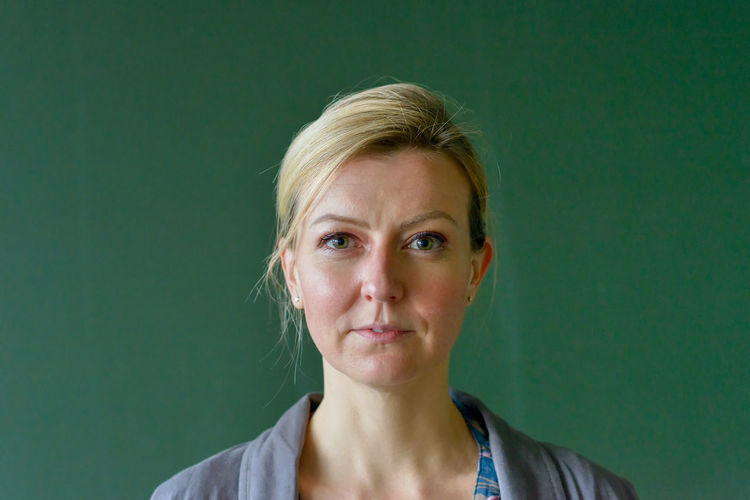 Portrait of mid adult woman against green background