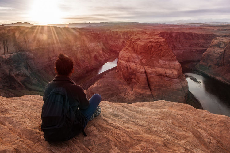 A young woman sits on the edge of cliff, and observes the grand view of Horse Shoe Bend before her. Arizona Breathtaking Breathtaking View Lost In The Landscape Relaxing Rock Formation Sitting Sitting Outside Sunrays Travel Travel Photography Traveling Colorado River Destination Female Horse Shoe Bend Mountain Range Observing Observing Nature One Person River Sitting Alone Sunset Travel Destinations Young Adult