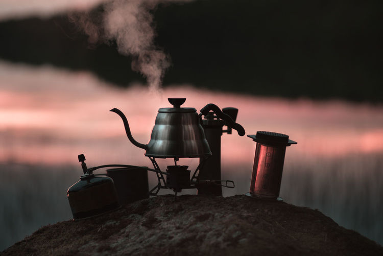 Boiling kettle and coffee or tea accessories in the evening or in the morning Coffee Time Drinks Hiking Appliance Burning Coffee - Drink Coffee Pot Drink Equipment Fire Heat - Temperature Household Equipment Kettle Kitchen Utensil Nature No People Outdoors Refreshment Sky Smoke - Physical Structure Stove Sunset Tea Kettle Teapot