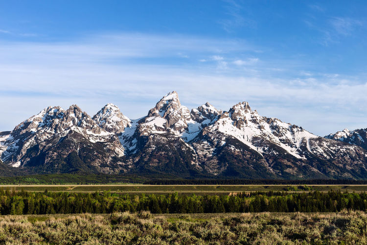 The snow-capped Grand Teton mountain range at dawn in Grand Teton National Park, Wyoming, USA. Grand Teton National Park  Grand Tetons Wyoming USA Sky Landscape Beauty In Nature Mountain Scenics - Nature Tranquil Scene Mountain Range Nature Mountain Peak Non-urban Scene Idyllic Tranquility Outdoors Land Wilderness Snowcapped Mountain Day Cloud - Sky Blue Background Travel Destinations