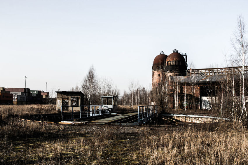 Leipzig Abandoned Architecture Bahnbetriebswerk Bare Tree Building Exterior Built Structure Clear Sky Damaged Day Lost Places In Leipzig Lostplaces Nature No People Old-fashioned Outdoors Retro Styled Run-down Sky Water Water Tower - Storage Tank Weathered Winter Wood - Material
