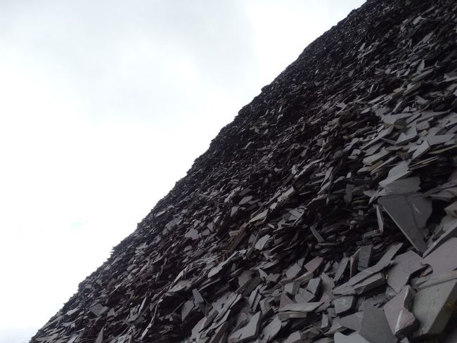 Slate pile against sky. Low Angle View Sky No People Day Outdoors Nature White Background Close-up Slate Pile Rocks Rock Formation Rock Slate Pile Quarry Slate Quarry Darkness And Light Hill Dull Slope Angle Slanted Rocky Rock - Object