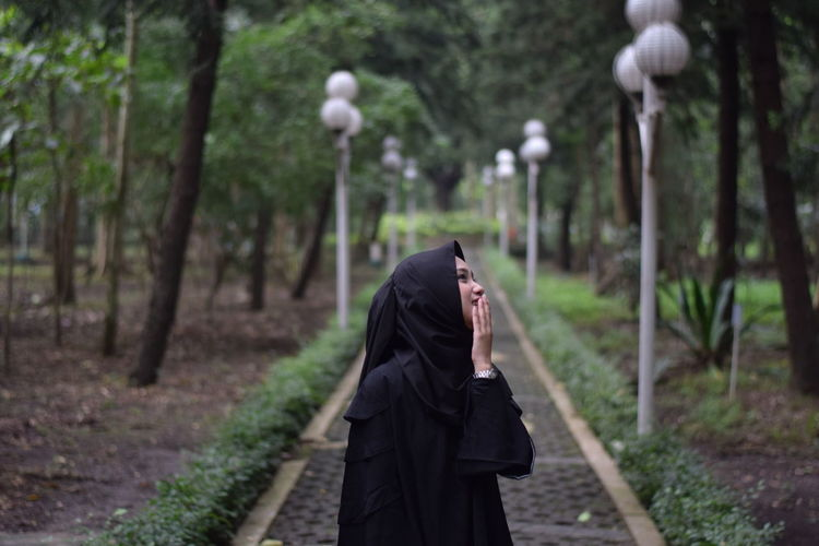 Smiling woman wearing hijab standing on footpath in park