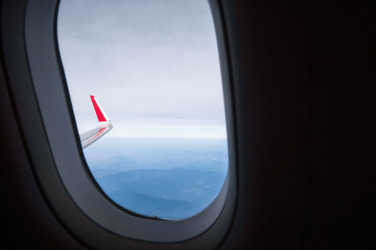 Airplane flying over landscape seen through window