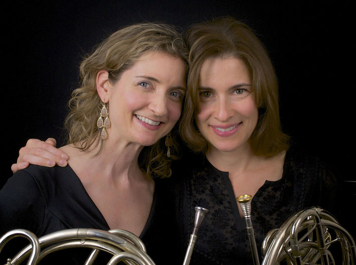 A pair of horns French Horn Opera Portrait Two People Looking At Camera Headshot Only Women Smiling Adult Adults Only Black Background Studio Shot Togetherness People Women Beautiful Woman Females Friendship Young Adult Happiness Human Face Young Women